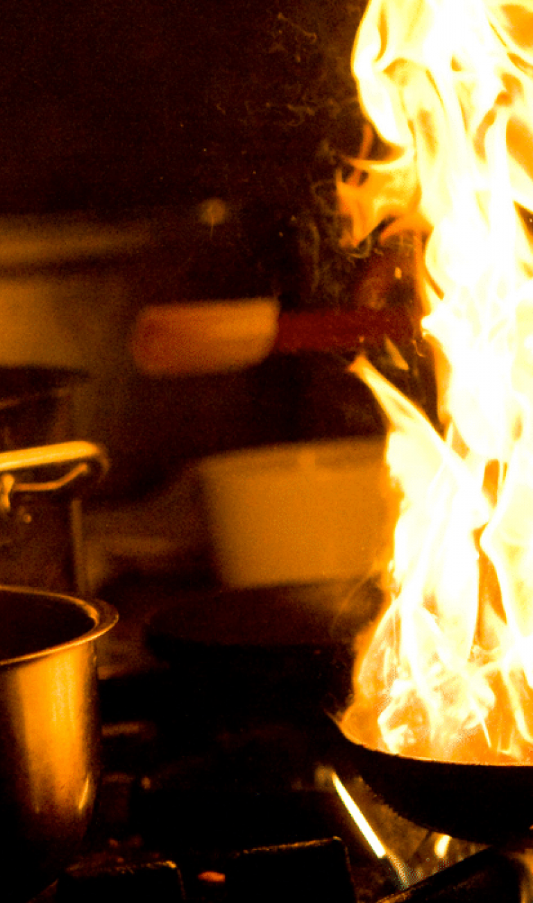 Flavor of the North Restaurant Month logo in green and black next to a chef cooking with flames coming out of a pot